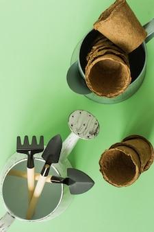 Садоводство в домашних условиях. выращивание еды на подоконнике. инструменты, торфяные горшочки и прессованная земля для рассады. вид сверху. flatlay на зеленом фоне.