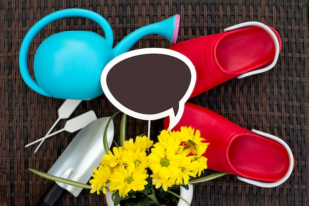 Gardening. autumn works in the garden. tools, watering can and flower in a pot on wicker rattan background.