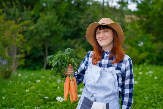 원예 - 채소 정원에서 유기농 당근을 든 아름다운 젊은 여성. 백라이트