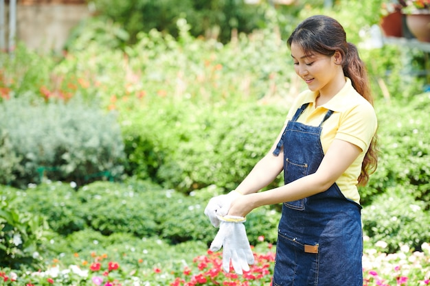 Gardening center worker putting on protective gloves when gettig ready to repot flowers