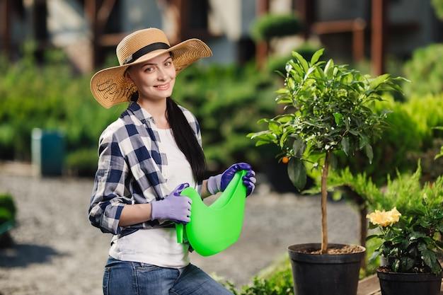 원예 개념. 뜨거운 여름 날에 정원에서 식물을 급수하는 아름 다운 여성 정원사의 초상화.