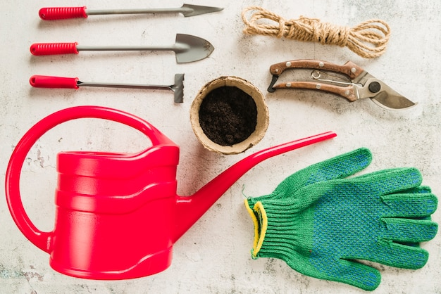 Gardening equipment; watering can; peat pot; secateurs; rope and gardening gloves on concrete backdrop