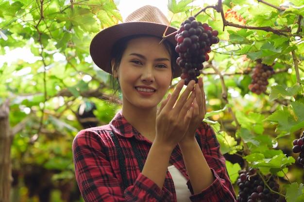ブドウ園でブドウを手に持った園芸少女。
