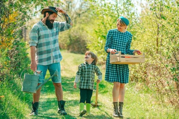 봄에 정원 가꾸기 행복한 가족 수확과 즐거운 시간을 보내는 농부 부부는 아들과 함께 즐거운 시간을 보내고 있습니다.