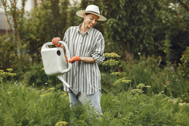 Садоводство летом. женщина поливает цветы из лейки. девушка в шляпе.