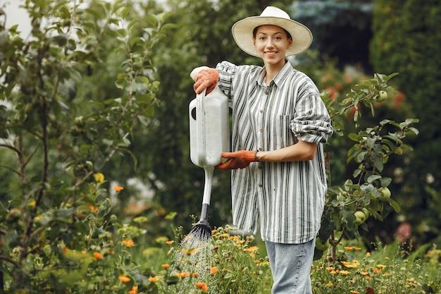 夏のガーデニング。水まき缶で花に水をまく女。帽子をかぶっている女の子。