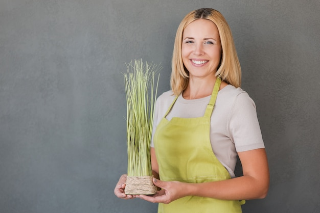 ガーデニングは私の情熱です。植木鉢を保持し、笑顔の緑のエプロンで陽気な成熟した女性