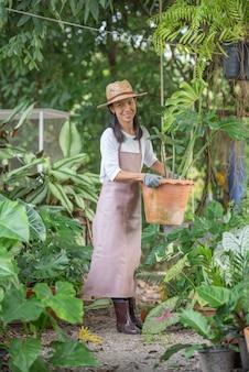 Giardinaggio, concetto di piantagione. imprenditrice scegliendo piante in vaso. felice giovane proprietario del negozio di alberi dell'asia che tiene vaso con una grande pianta di monstera e sorride.