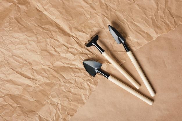 Садовый набор маленьких граблей и лопат на коричневой крафт-бумаге, копировальное пространство, вид сверху