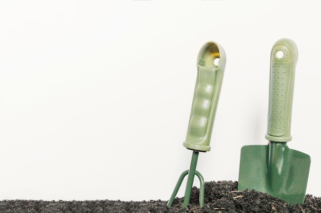 Gardening shovel and gardening rake in plain black soil against isolated on white background