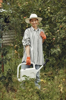 Gardening in summer. woman watering flowers with a watering can. girl wearing a hat.
