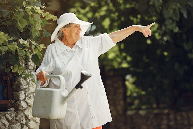 Gardening in summer. woman watering flowers with a watering can. old woman wearing a hat.