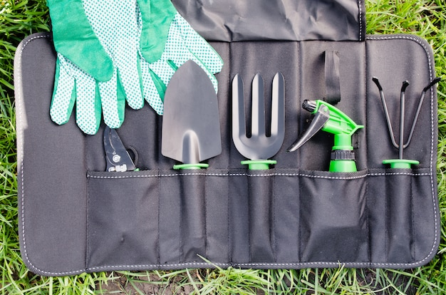Gardening tools in the bag on the grass.