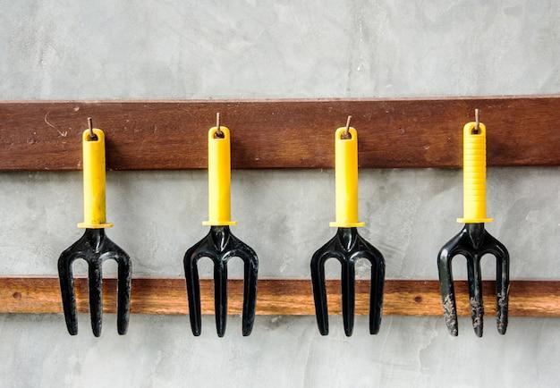 Gardening tools, black iron rake with plastic handle hanging on wall