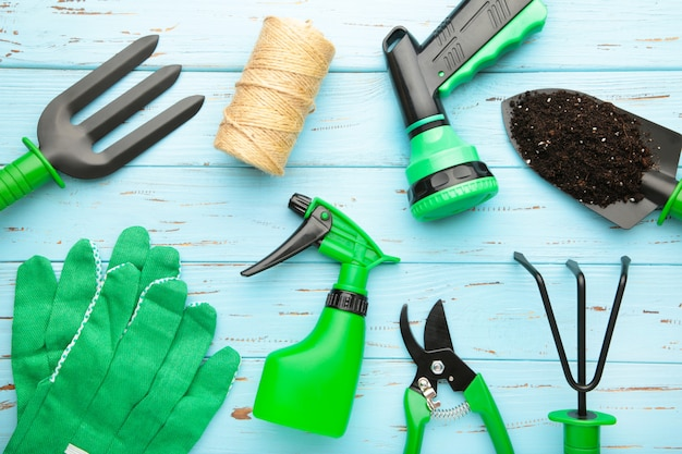 Gardening tools on blue wooden background, top view