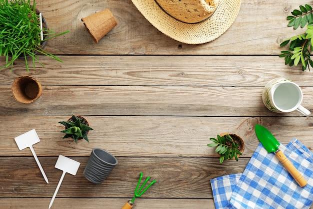園芸工具、ポット、草、およびヴィンテージの木製の背景に麦わら帽子の花。