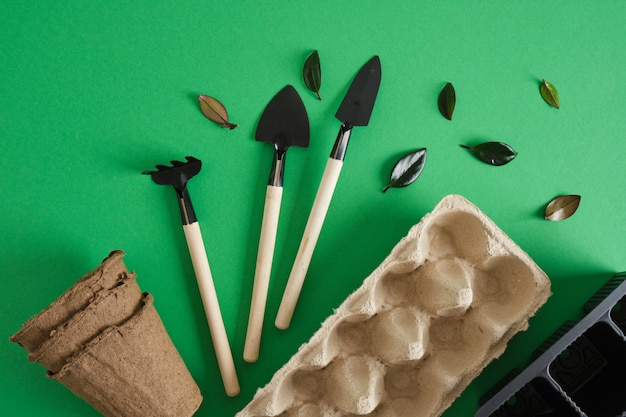Gardening tools on green background. small shovels and rakes for planting seedlings and indoor plants, eco friendly gardening concept