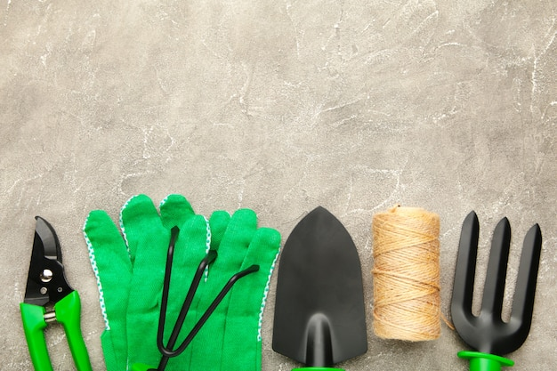 Gardening tools on grey concrete background, top view