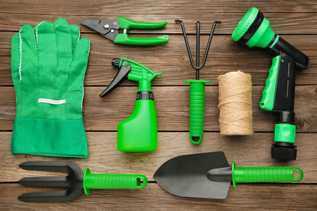 Gardening tools on grey wooden background, top view