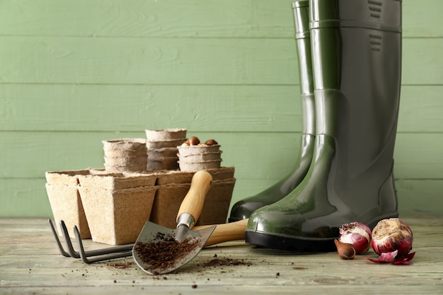 Gardening tools and gumboots on wooden