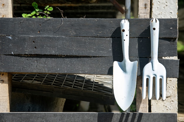 Gardening tools hang on wooden rail