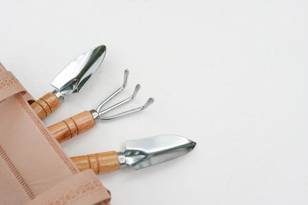 Садовничая инструменты в сумке на белой стене. копировать пространство