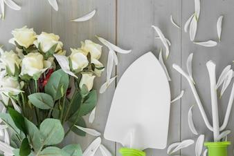 Gardening tools near roses and petals