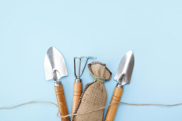 Садовые инструменты на синей стене с копией пространства