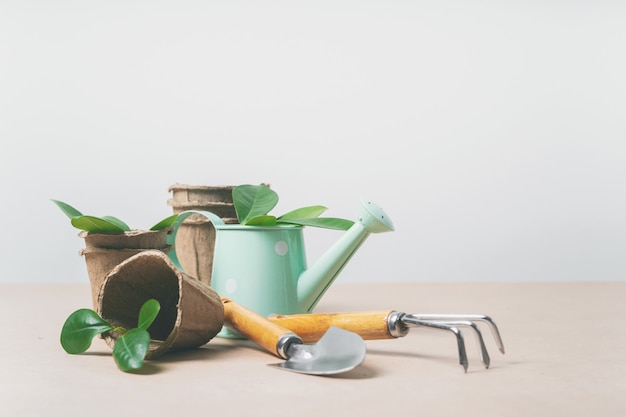 Gardening tools, paper pots, watering can on craft paper with copy space.