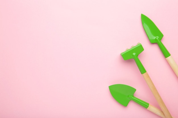Gardening tools on pink surface with copy space