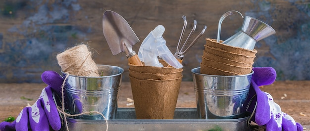 Gardening tools, pots and utensils on rustic wooden background, banner