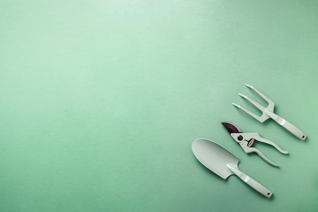 Gardening tools and utensils on green background. pruner, rake, shovel for garden manteinance.