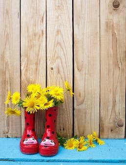 園芸工具、水やり、種子、植物、土壌。木製の背景に鉢植えの花