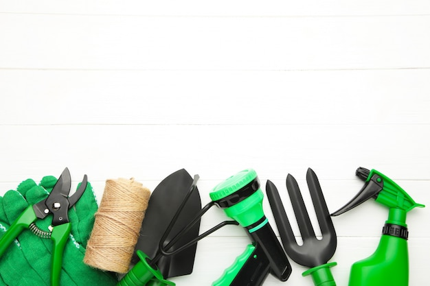 Gardening tools on white wooden background, top view