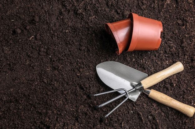 Gardening tools with pots on soil