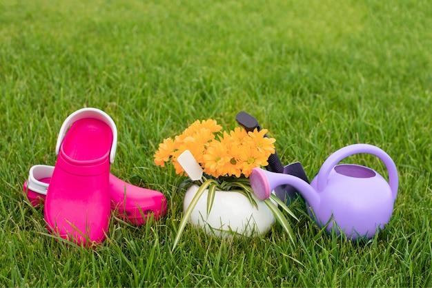 園芸。庭の仕事。ツール、水まき缶、緑の葉の背景に鍋に花。スペースをコピーします。暗い背景の木。