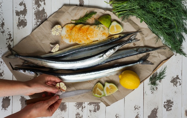 Garfish, billfish  raw and fresh, top view, with onions, lemon, prepared for cooking