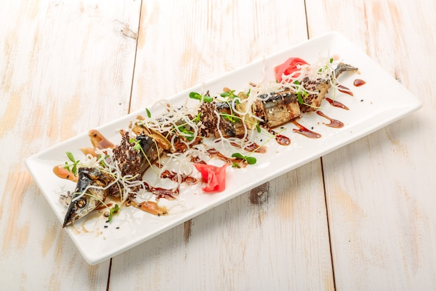 Garfish with vegetables, fried garlic fish on white wooden background