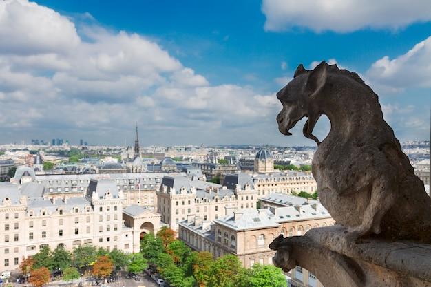 Дракон-горгулья из парижа на соборной церкви нотр-дам и городской пейзаж парижа, франция