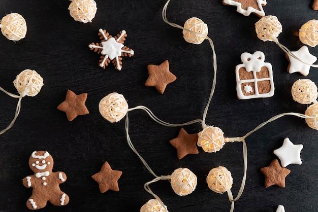 ガーランドとクリスマスのクッキーは、黒い背景に砂糖のアイシングを釉薬をかけました。