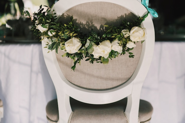 Garland of beautiful white roses hangs on the back of grey chair