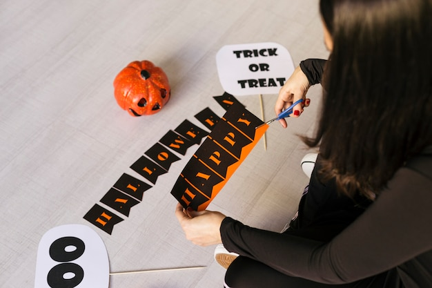 若い女性はハロウィーンgarland.creative diyを作ります。家の装飾プロジェクトパーティー。ハロウィーンクラフトのインスピレーション。
