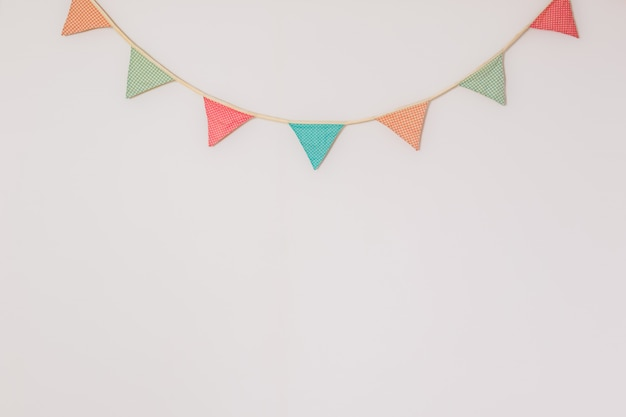 Garland of cute party flags hanging on the wall. background with copyspace symbolising home celebration, birthday or festive mood