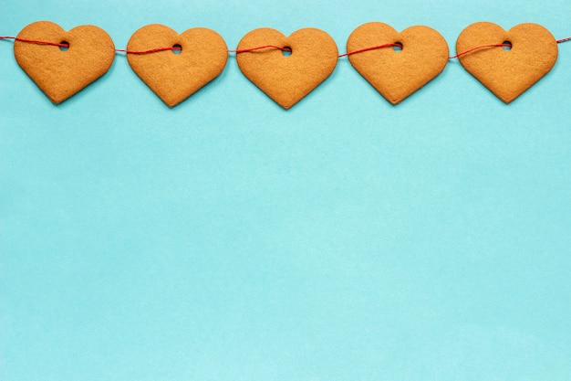Garland of ginger cookies in shape of hearts on red ribbon