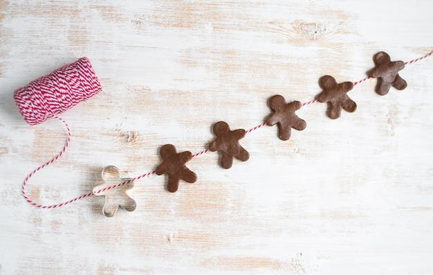Garland gingerbread man red yarn fir tree brunch dough christmas concept new year party