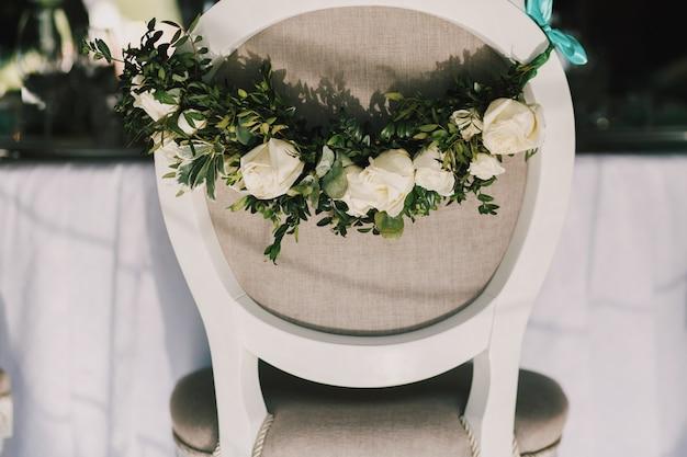 아름다운 흰 장미 화환이 회색 의자 뒷면에 달려 있습니다.
