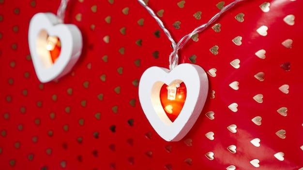 赤い背景の上の木の心のガーランド。バレンタイン・デー