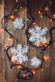 Garland and snowflakes on the wooden table