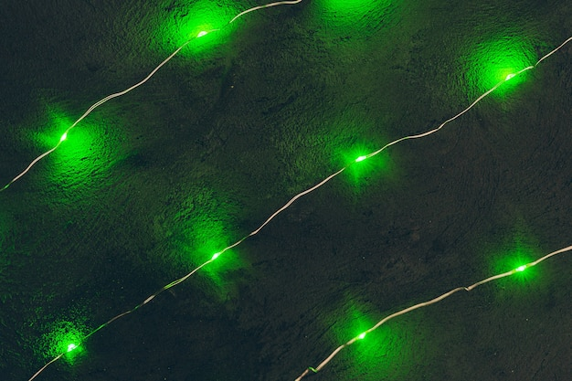 Garland with green light elements in the dark close up