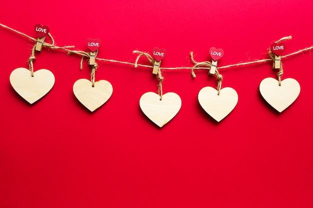 Garland of wooden hearts with clothespins with the inscription love on a red background. valentine's day, copy space, holiday lights, flyer, lovers